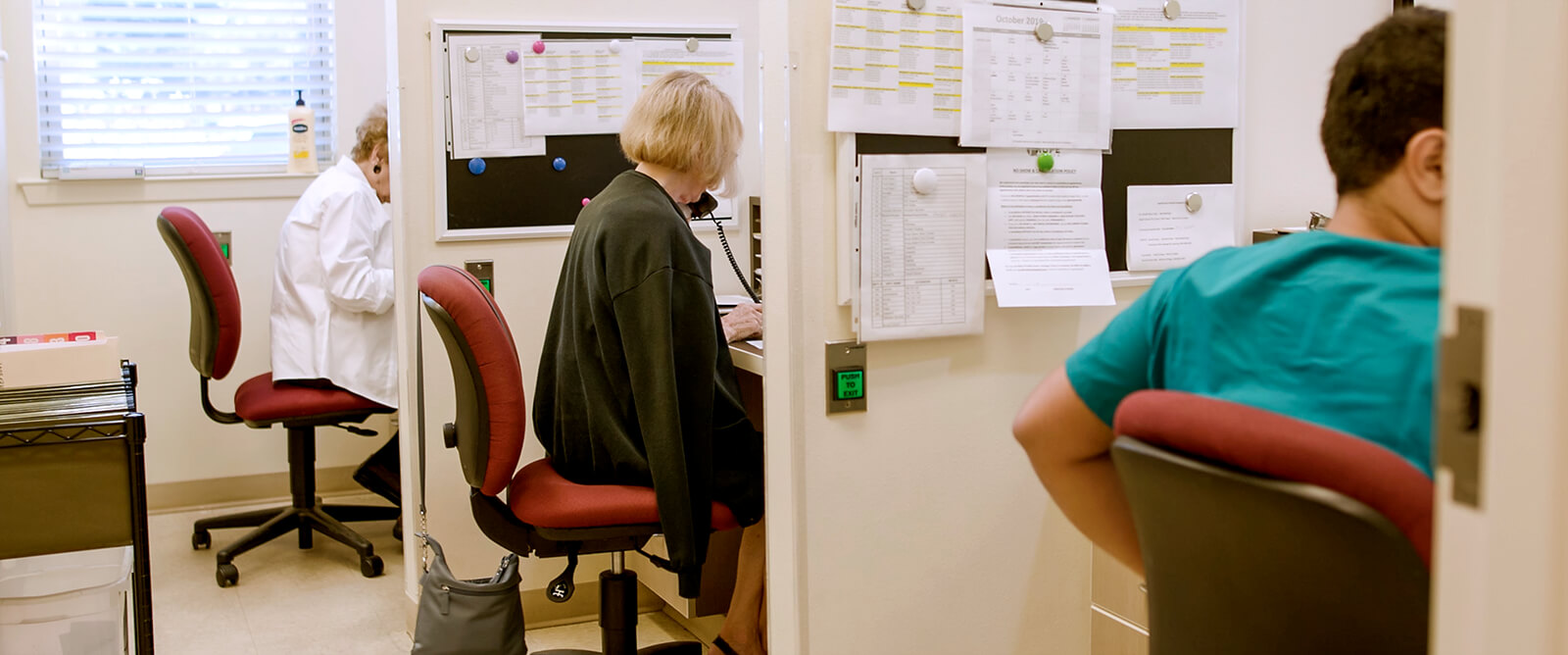 Photo: Three Clinic volunteers working in the phone cubicles at Clinic's scheduling area
