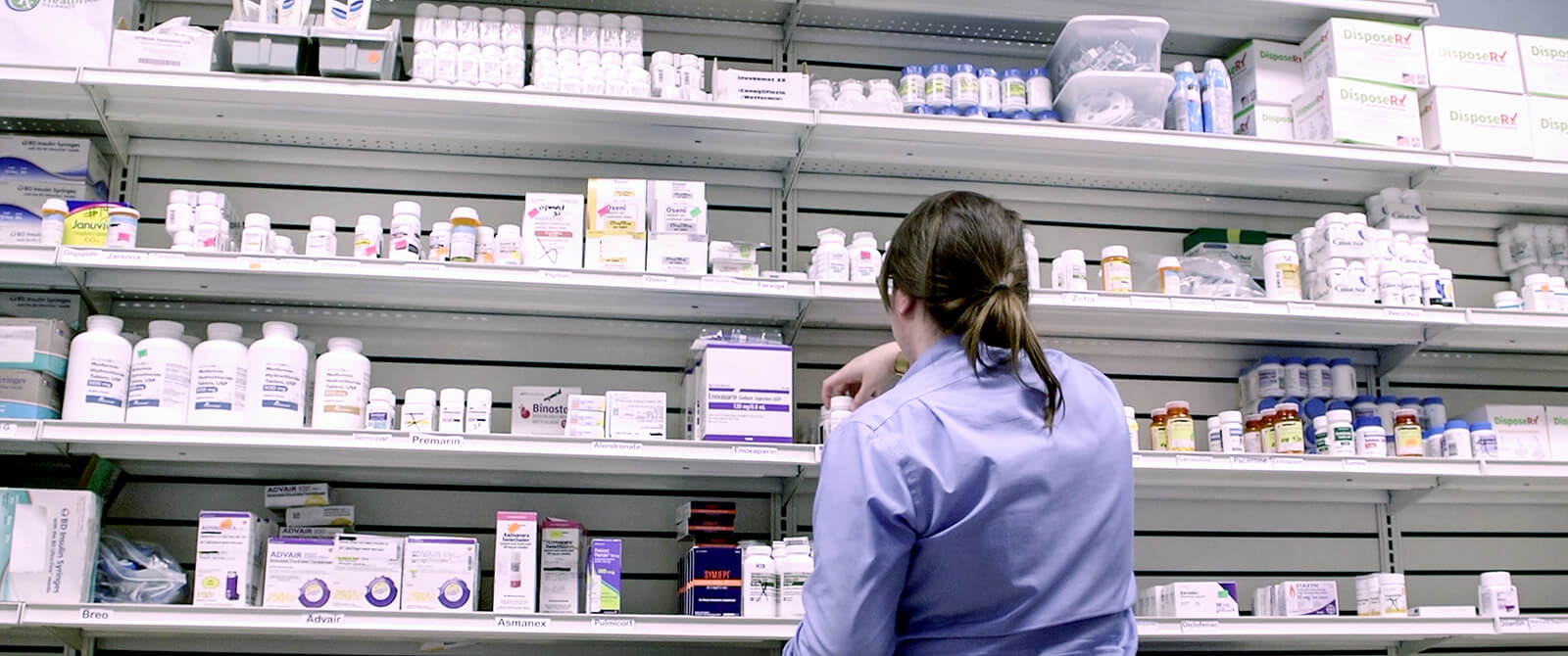 Photo: A volunteer pharmacy worker stocks the shelves of the Clinic's in-house pharmacy
